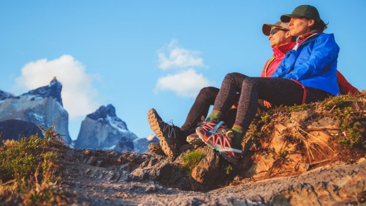 Two hikers in Torres del Paine sitting and watching sunset.