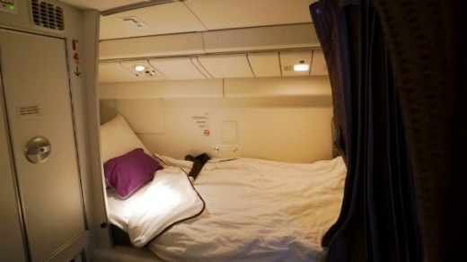 Flight attendants sleep in the area above economy class that has eight single beds with sheets, blankets and pillows.