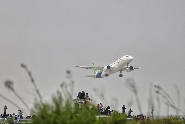 Spectators outside the airport takes photos of a C919.