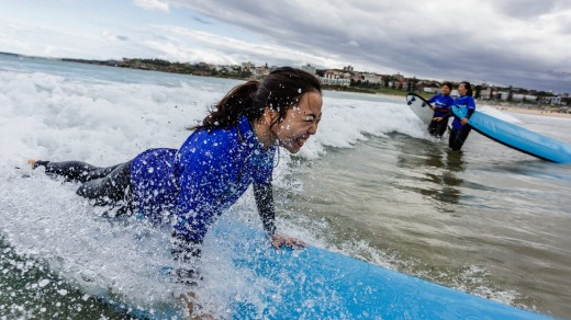 A Chinese visitor gets a surfing lesson at Bondi Beach.