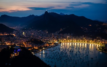 Christ the Redeemer statue lit up against the dark sky, watching over Rio.