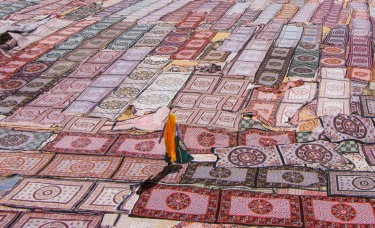 A Rajasthani lady walking across a sea of textiles laid out to dry.