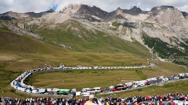 Spectators, cyclists, campervans and team buses line the roads at the bottom of the Col du Galibier.