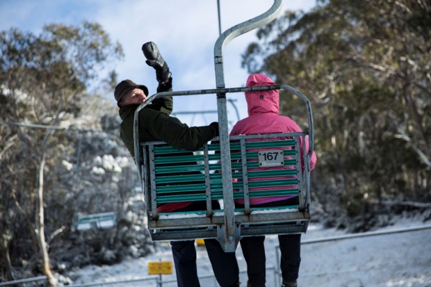 Couple riding chairlift through snow covered trees at Thredbo Ski Resort.