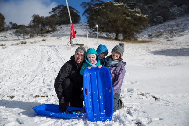 A family enjoys tobogganing at Thredbo Ski Resort after a large dump of snow over the weekend.