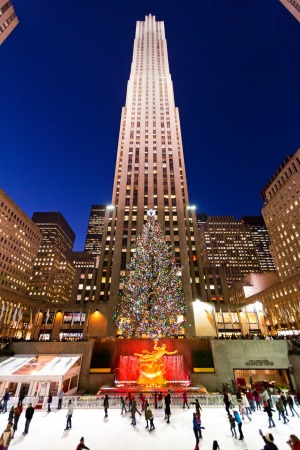 Ice skaters on the ice rink at Rockefeller Center with the famous Christmas tree. Rockefeller is a landmark complex of ...