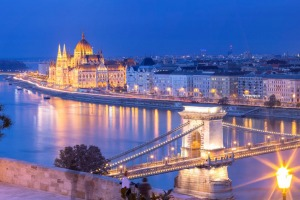 Panoramic view of the Hungarian Parliament Building and the Szechenyi Chain Bridge in Budapest at dusk.