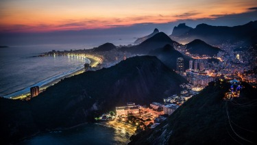 At the Sugarloaf Mountain in Rio, watching the sky turn into shades of red and orange as the sun sets, with sea glisten ...