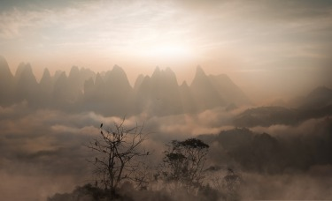 Dawn broke over hundreds of oddly shaped karst mountains bathed in fog on a spring morning.  The town that lies beneath ...