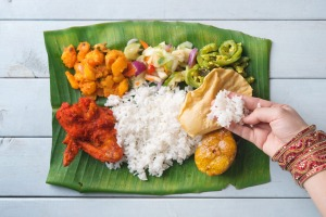 Indian woman eating banana leaf rice, overhead view on wooden dining table. SatJun17cover-WorldFood - Ben Groundwater ...