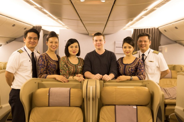 Sixteen-year-old travel blogger Zac George, pictured with cabin crew from Singapore Airlines, became the youngest person ...