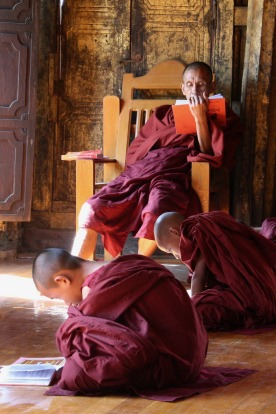 These novice monks are studying their lessons under the direction of their teacher, as the morning sun streams in the ...