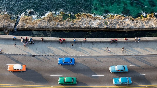 Cars speeding along the Malecon in Havana.
