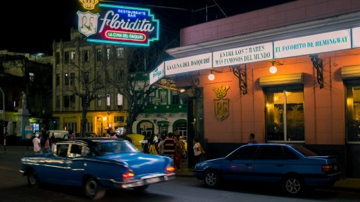 Vintage car passing by at night next to the famous Floridita bar in old Havana.