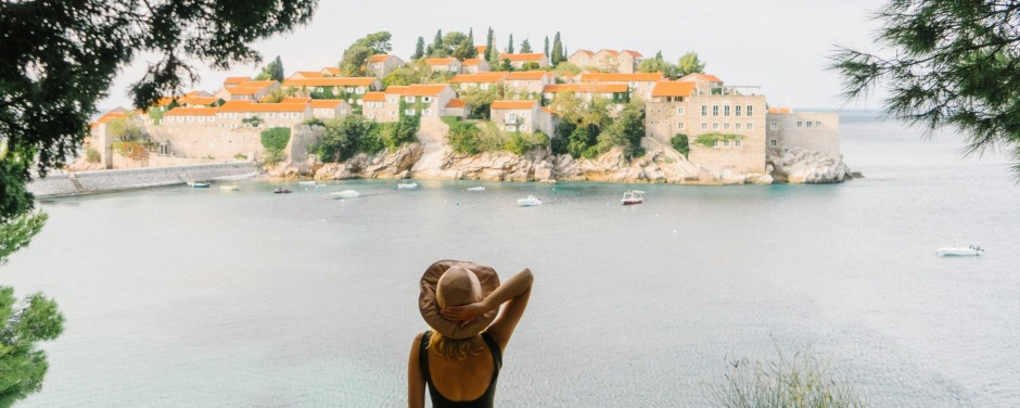 Woman standing on the background of Sveti Stefan island, Montenegro SunJune18cover-LittleWonders Credit: iStock ...