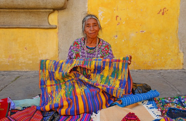 A Mayan saleswomen showing her textiles in the local arts and crafts market in Antigua, Guatamala.