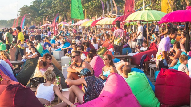 Tourists enjoy a drink in a beach bar along Seminyak beach, just north of Kuta, in Bali.