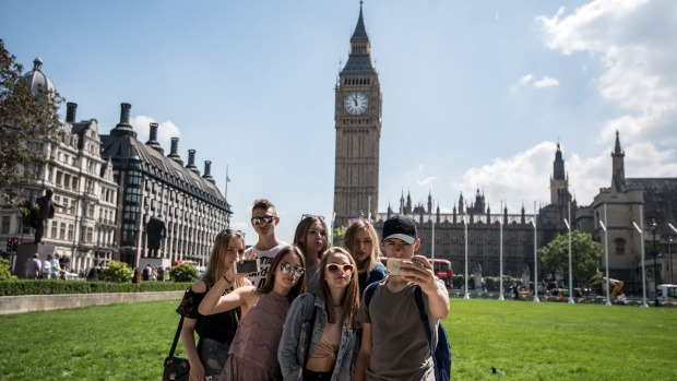 Young tourists take a group selfie in Parliament Square.
