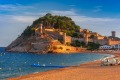 Fortress and fishing boats at Gran Platja beach and Badia de Tossa bay in the evening in Tossa de Mar on Costa Brava, ...