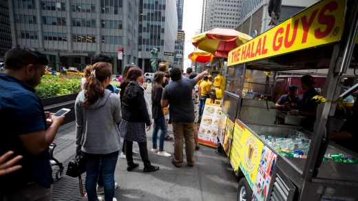 Customers queue at The Halal Guys' food cart on West 53rd Street and 6th Avenue.