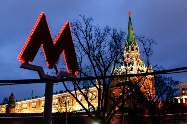 Glowing Moscow metro sign and the Kremlin tower.