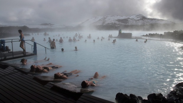 Guests relax in geothermal seawater in the main lagoon at the Blue Lagoon spa in Grindavik, Iceland,