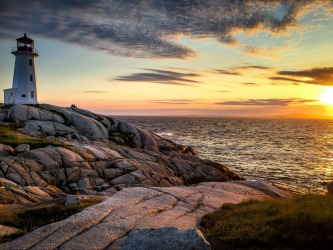 Sunset view of Peggy's Point Lighthouse at Peggy's Cove, Nova Scotia. If you look carefully, you can see a family to the ...