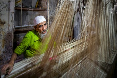 In the back laneways of Varanasi, India a small doorway led to the darkened confines of a weaving room. With only one or ...
