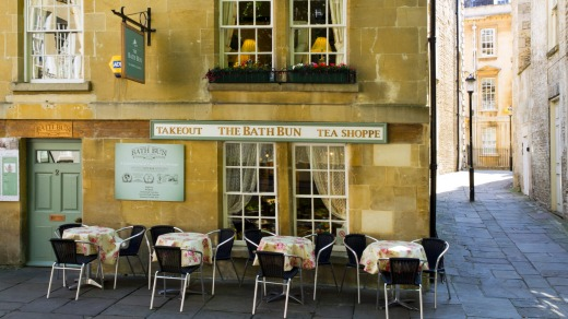 Outdoor tables ready for customers on a shady street near Bath Abbey.