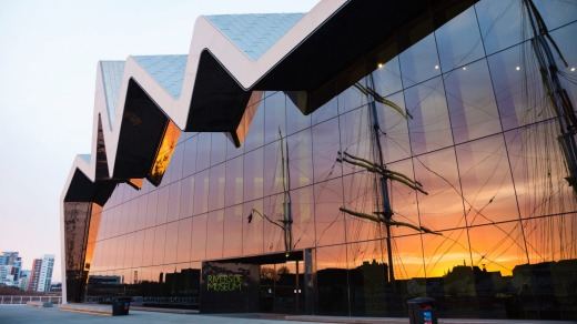 The Riverside Museum in Glasgow. Reflected in the glass facade are the masts of the Victorian tall ship Glenlee.
