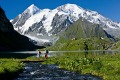 Hikers along Lake Louvie with the Louvie hut at 2207 m in Canton Valais. View across the Bagnes valley towards the ...
