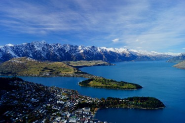 The scenic view of The Remarkables Mountain Range & city of Queenstown, New Zealand. As seen from the Skyline ...