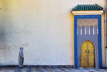 A local man dressed in the traditional Morrocan overcoat, the Djellaba, walking past the Royal Palace in Fes.