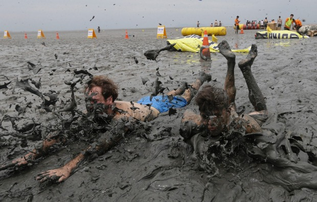 Men slide in the mud during the Boryeong Mud Festival at Daecheon Beach in Boryeong, South Korea. The 20th annual mud ...