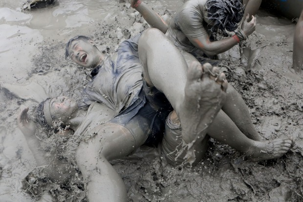 Festival-goers enjoy during the annual Boryeong Mud Festival at Daecheon Beach in Boryeong, South Korea. The mud, which ...