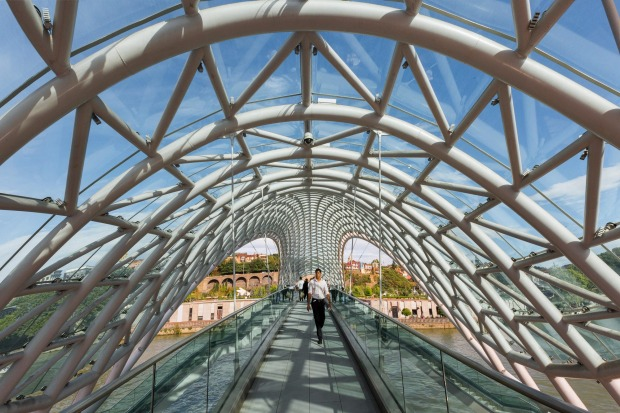 BRIDGE OF PEACE, GEORGIA- Beneath an arching honeycomb of white steel, this glass-sided suspension bridge is implanted ...