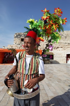 A tea vendor in traditional dress in the ancient town of Gadara.