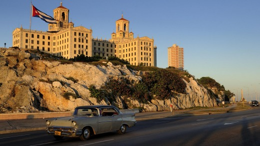 One of Havana's many classic 1950s cars drives past former Mob-owned Hotel Nacional.