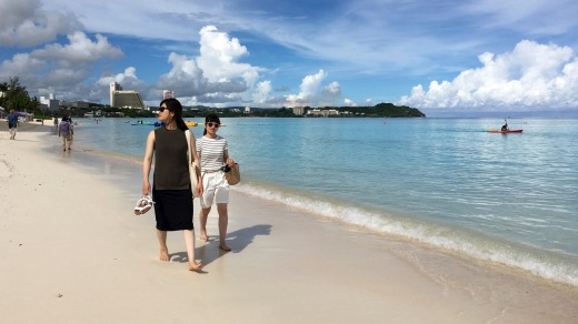 Tourists walk the beach in Tumon, Guam after North Korea's threat this week.
