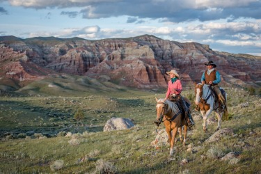 Wranglers ride off into the setting sun at the CM Ranch, near Dubois, Wyoming, USA. Dubois is a small town not far from ...