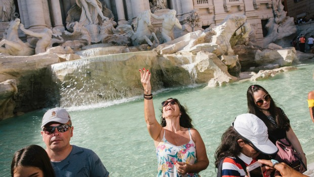 A tourist throws a coin in the Trevi Fountain in Rome.