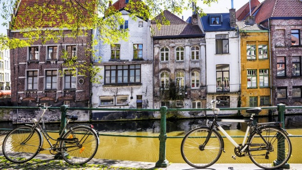 Bicycles parked by the canal in front of the old medieval houses in Ghent.