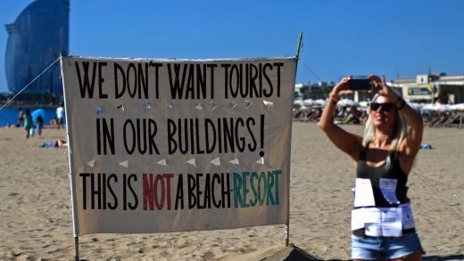 A woman takes a picture during a protest against tourism in Barcelona.
