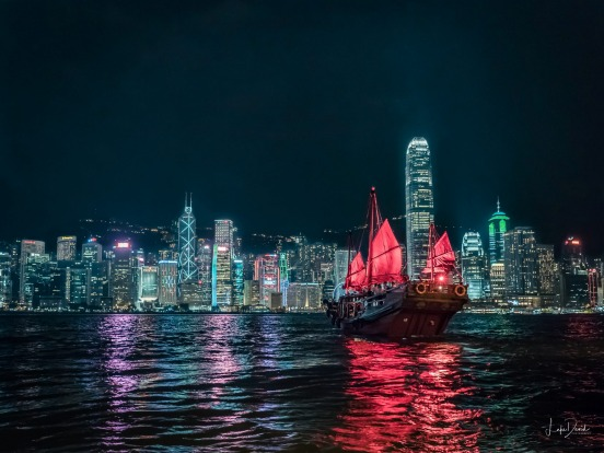 Taken on Victoria Harbour in Hong Kong, the old and the new glow with life. A red sailed Junk carries a load of tourists ...