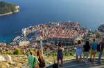 Popular summer travel destination: Tourists at a vantage point looking at the Old Town of Dubrovnik in Croatia from above.