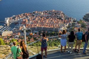 Tourists at a vantage point looking at the Old Town of Dubrovnik in Croatia from above.