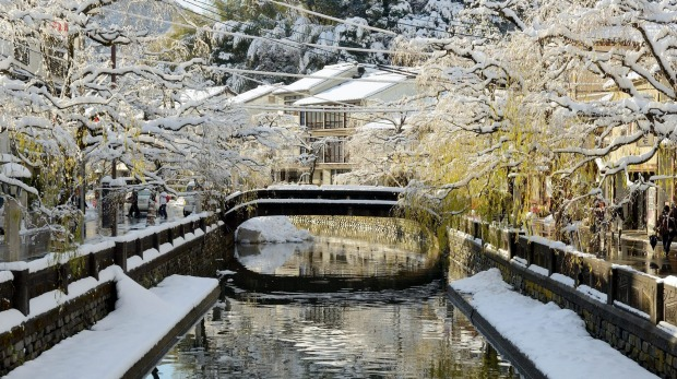 A bridge in Kinosaki Onsen covered by snow.