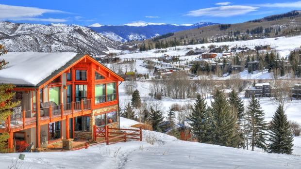 Snowmass - a ski resort with a background of a small residential area (small huts) surrounded by trees.