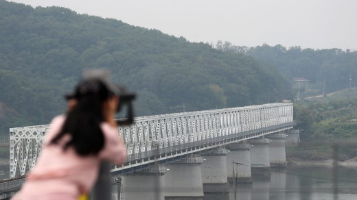 A visitor uses binoculars to look across to the north side of the border at the Imjingak pavilion near the Demilitarized ...