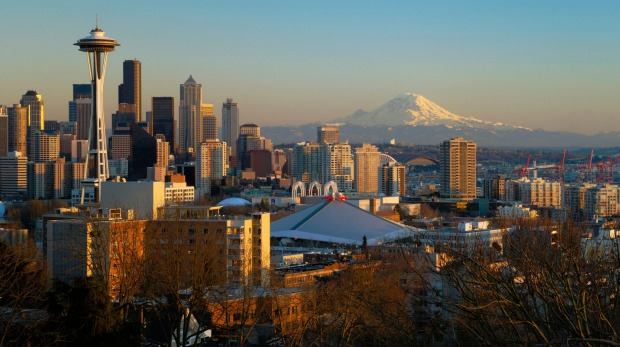 The Seattle city skyline at sunset with the Space Needle, downtown and Mount Rainier from Queen Anne Hill.